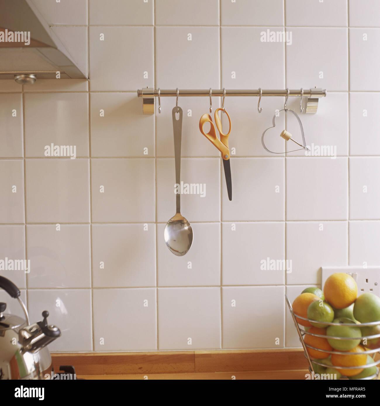 Utensili da cucina appesi da ganci di acciaio su bianco parete ...