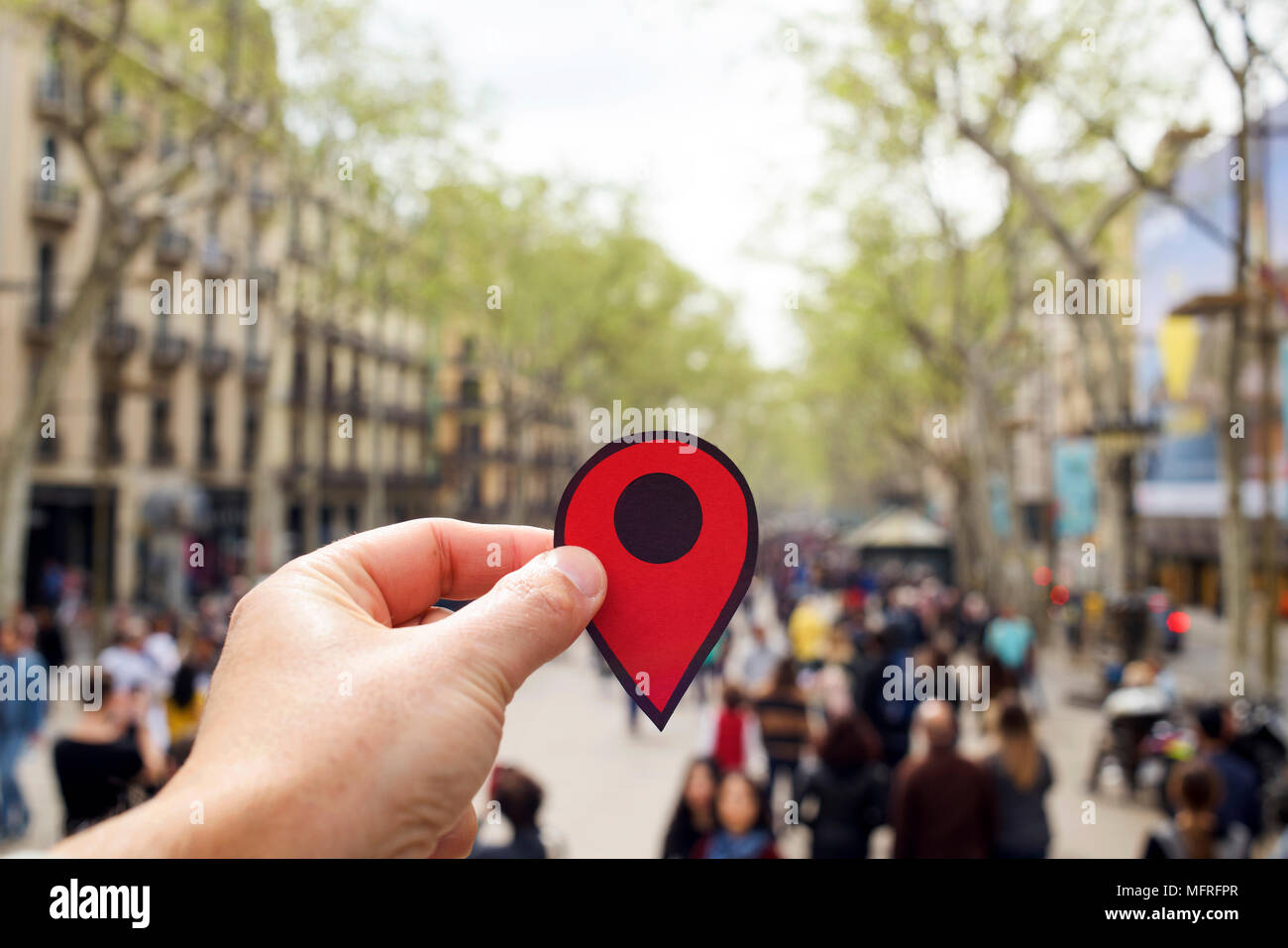 Primo piano della mano di un giovane uomo caucasico con un indicatore rosso nella famosa Las Ramblas, Barcelona, Spagna Immagini Stock