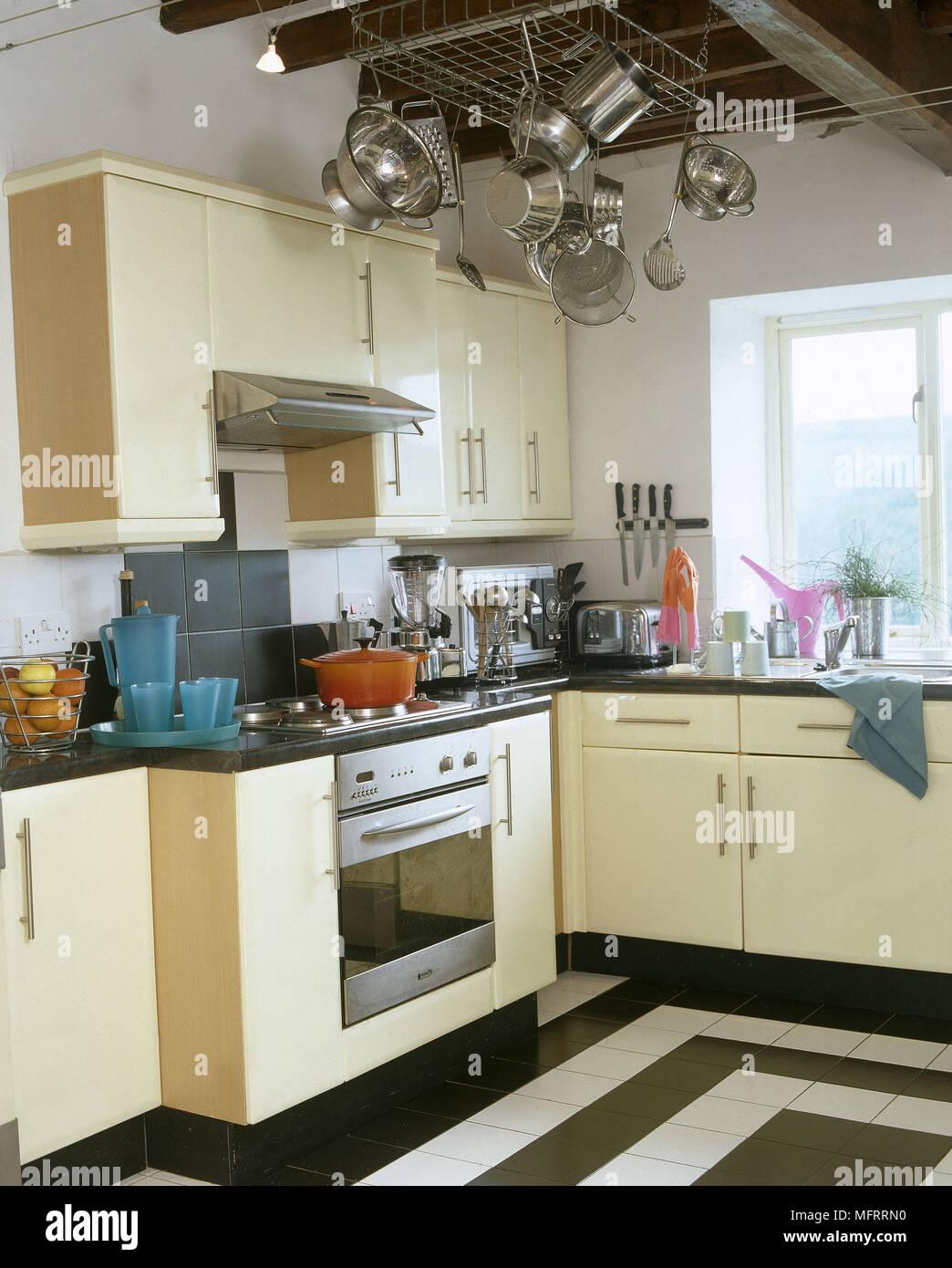 Una cucina moderna con crema di granito unità tops appeso pentole ...