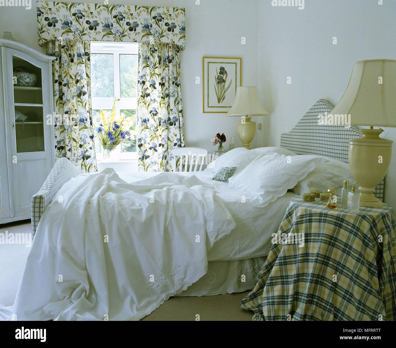 Camera da letto con lenzuola bianche sul letto e motivi floreali ...
