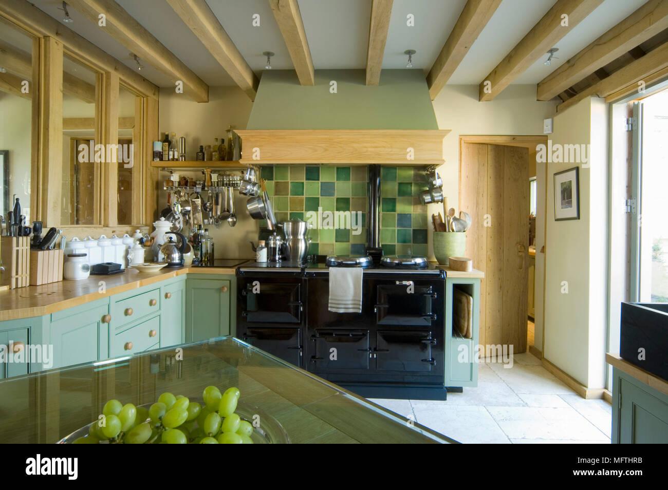 Cucina con fornelli accanto al verde parete piastrellata e travi