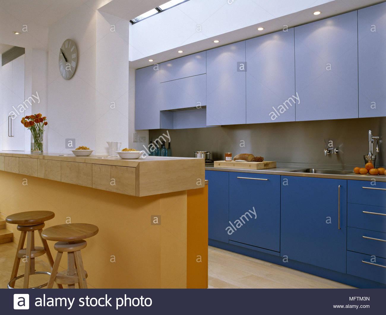 Una cucina moderna con armadi blu breakfast bar e sgabelli in legno