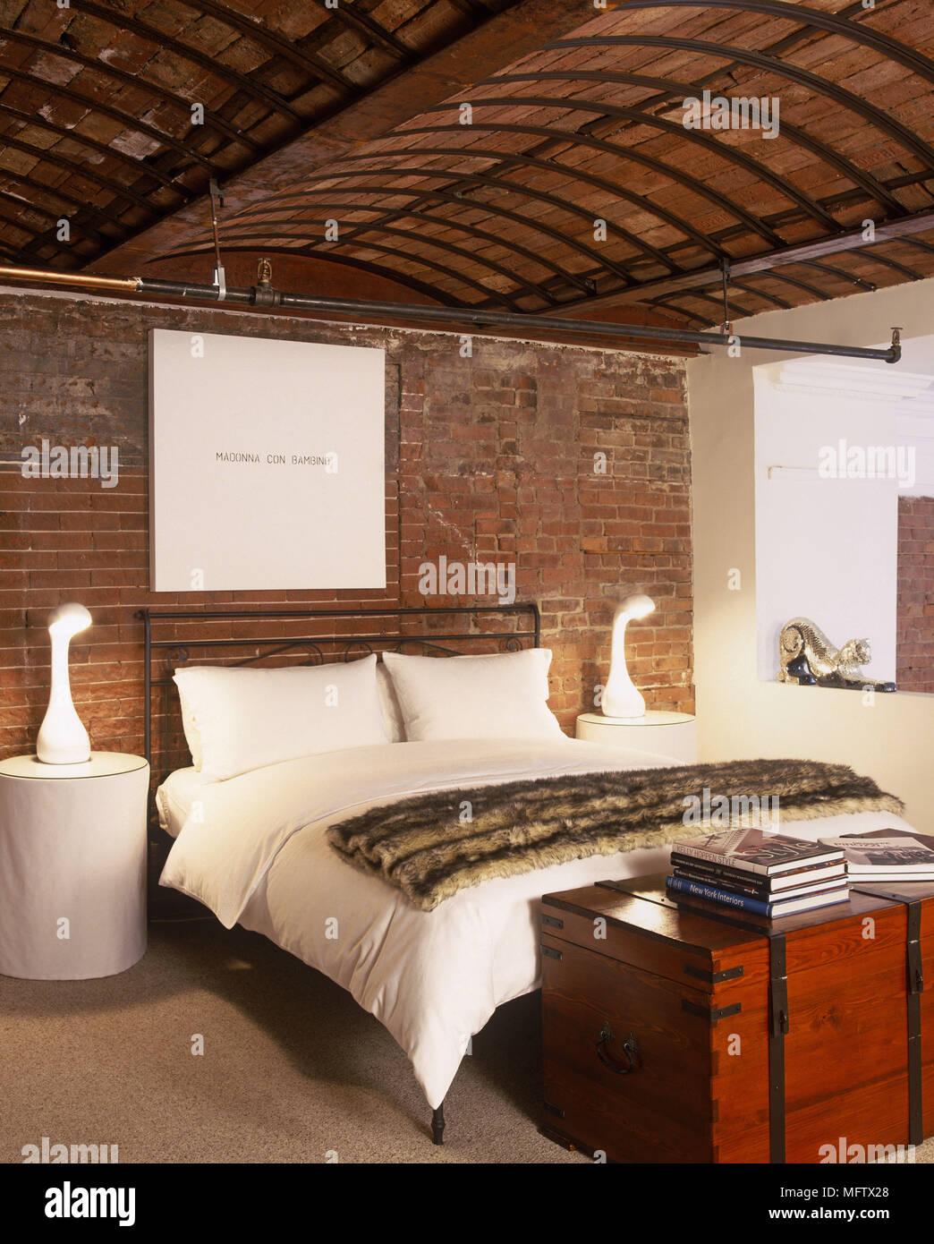 Lampade sulle tavole rotonde su entrambi i lati del letto ...