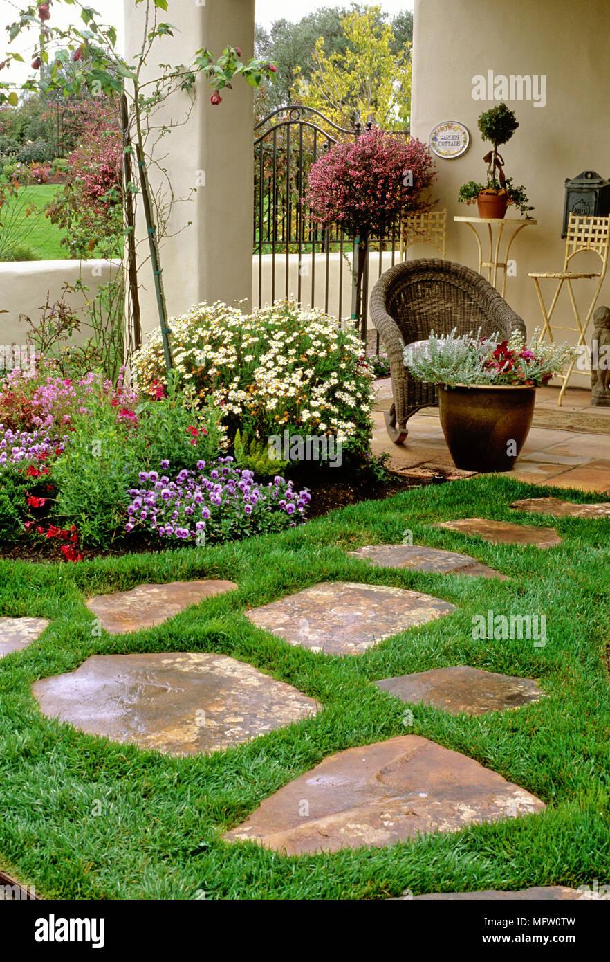 Pietre per pavimentazione impostato in erba nel giardino con una piantagione di viola e di - Giardini con pietre bianche ...