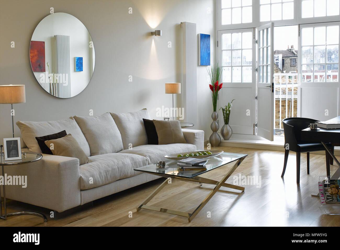 Specchio circolare al di sopra di un divano in soggiorno con ...