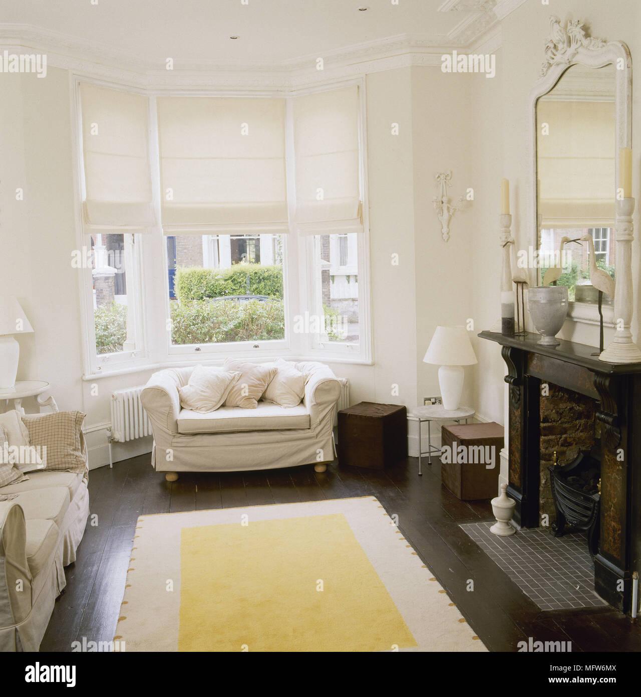 Tradizionale salotto con pavimento in legno divani imbottiti camino ornato di specchio e tende - Finestra a bovindo ...
