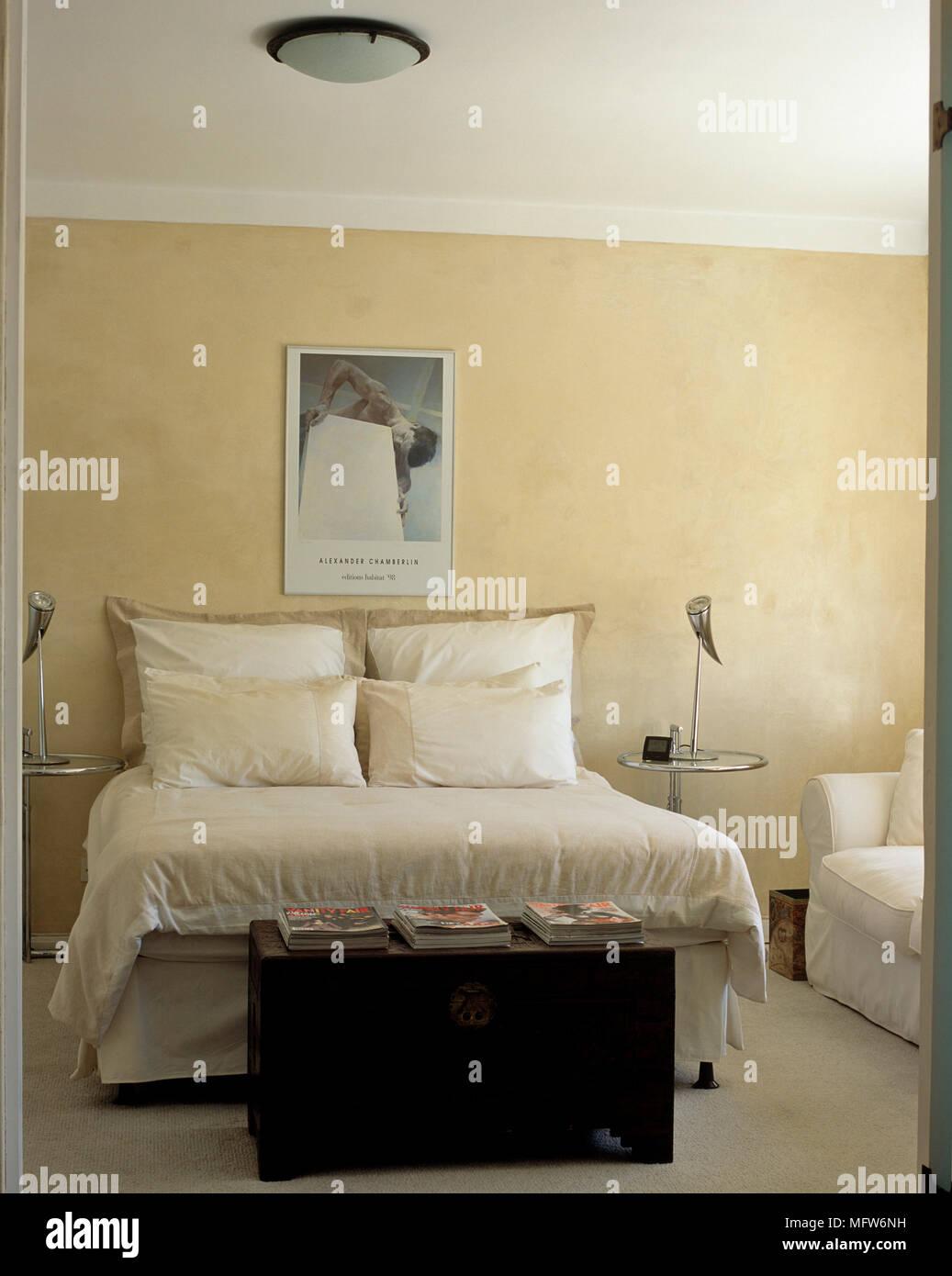 Cassa di legno ai piedi del letto matrimoniale sul colore neutro ...