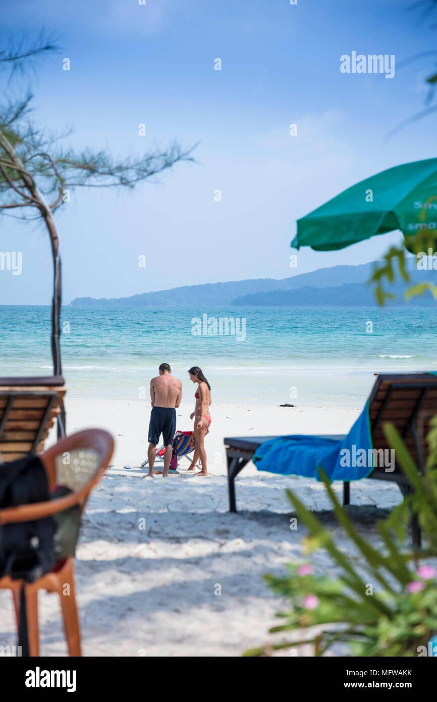Candide colpo di una giovane coppia di parlare su una spiaggia di sabbia bianca su di un isola nel sud-est asiatico Immagini Stock