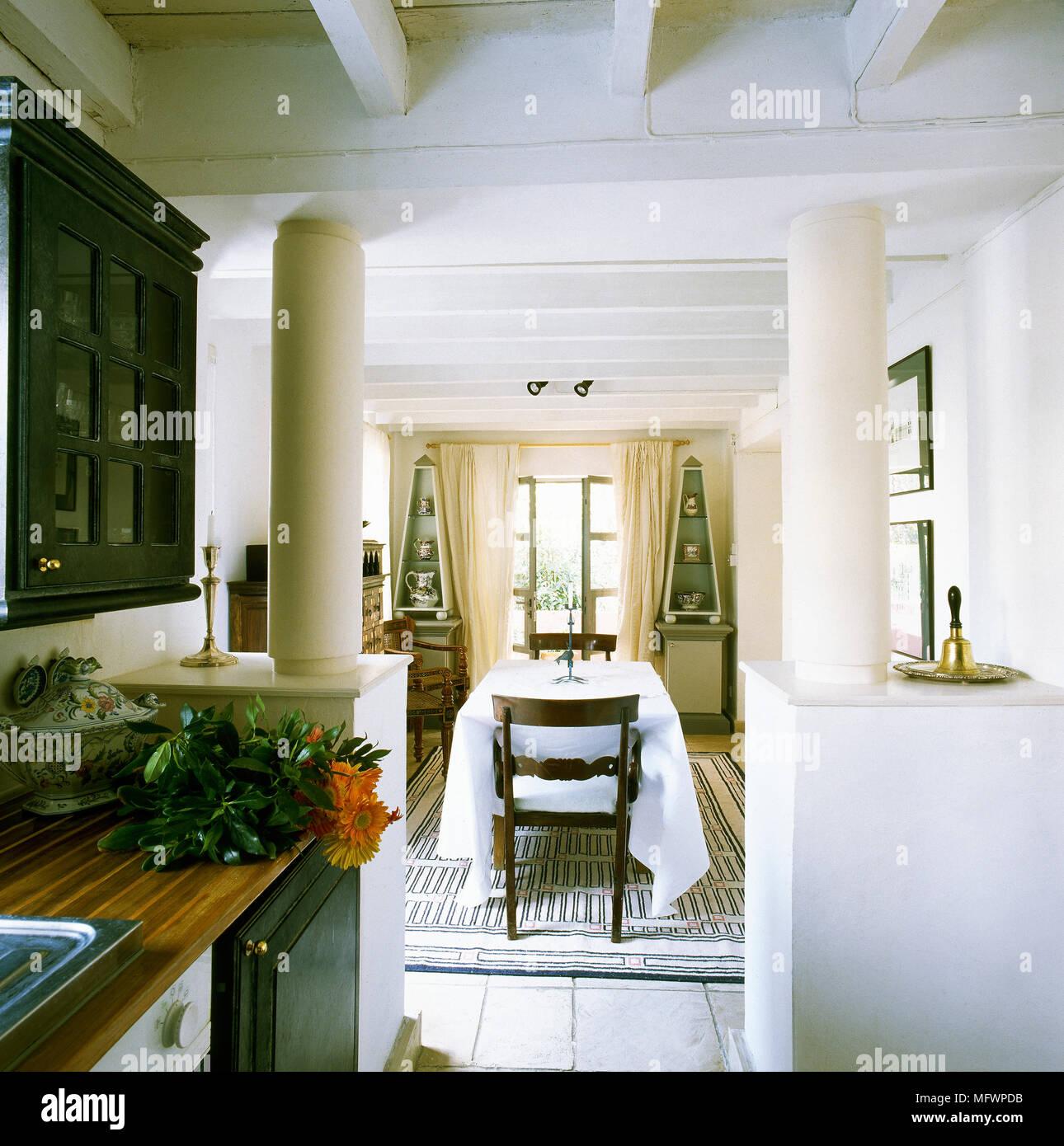 White cucina con sala da pranzo al di là con tavolo e sedie Foto ...