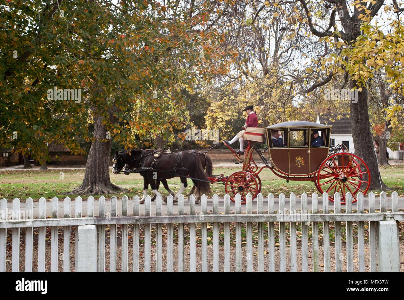 Un cavallo disegnato ripristino carrello e lentamente il driver fanno la loro strada verso il basso N. Queen St. in Williamsburg Coloniale con la Picket Fence in primo piano Immagini Stock