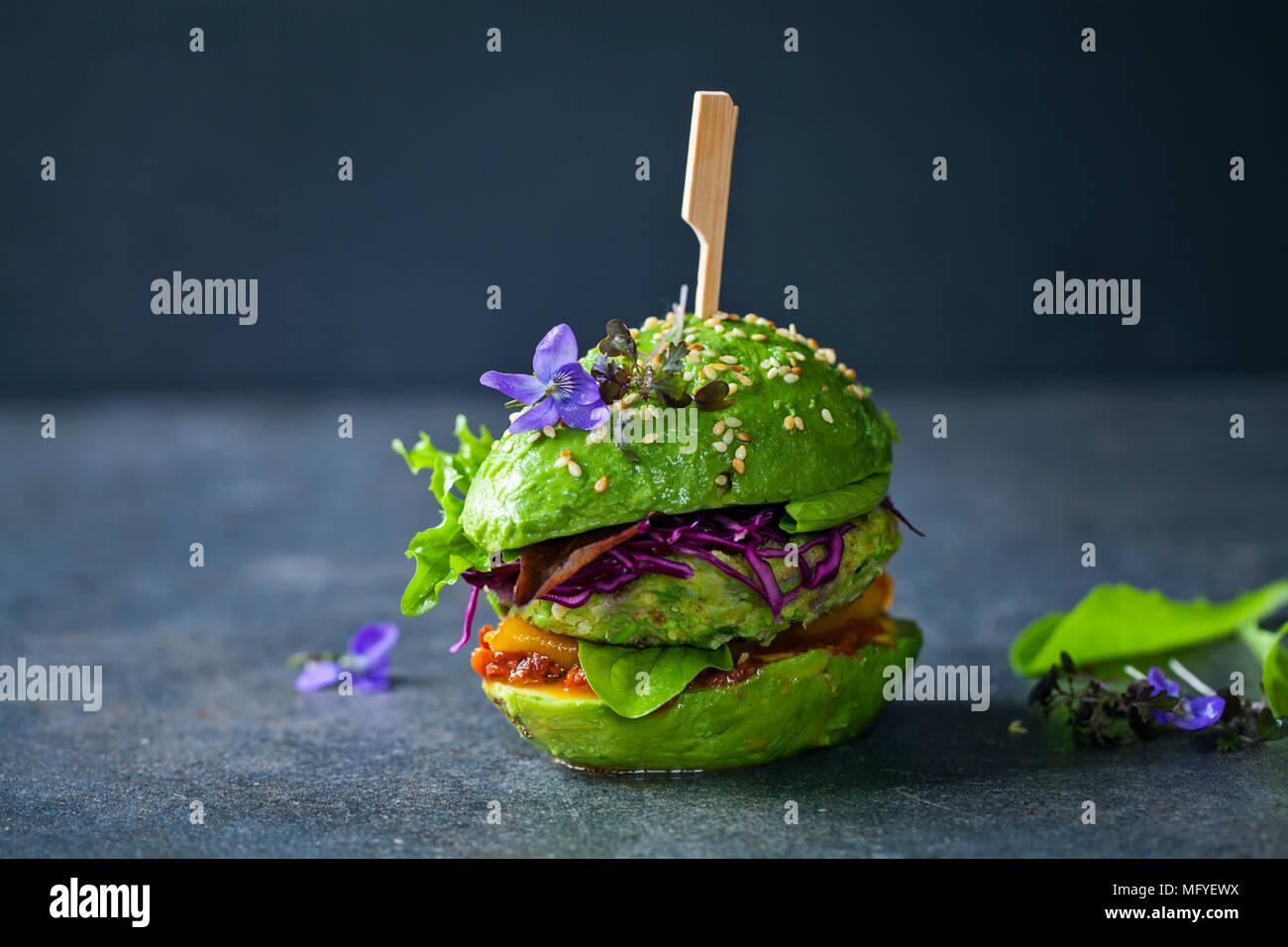 Sandwich di Avocado con green vegan burger, arrosto di peperone giallo e decapati cavolo rosso Immagini Stock