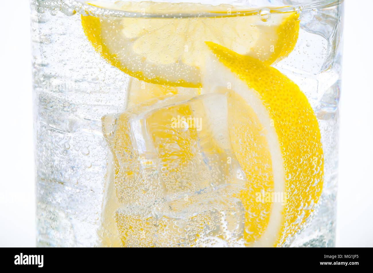Ghiaccio, le fette di limone e acqua trasparente in un vetro. Immagini Stock