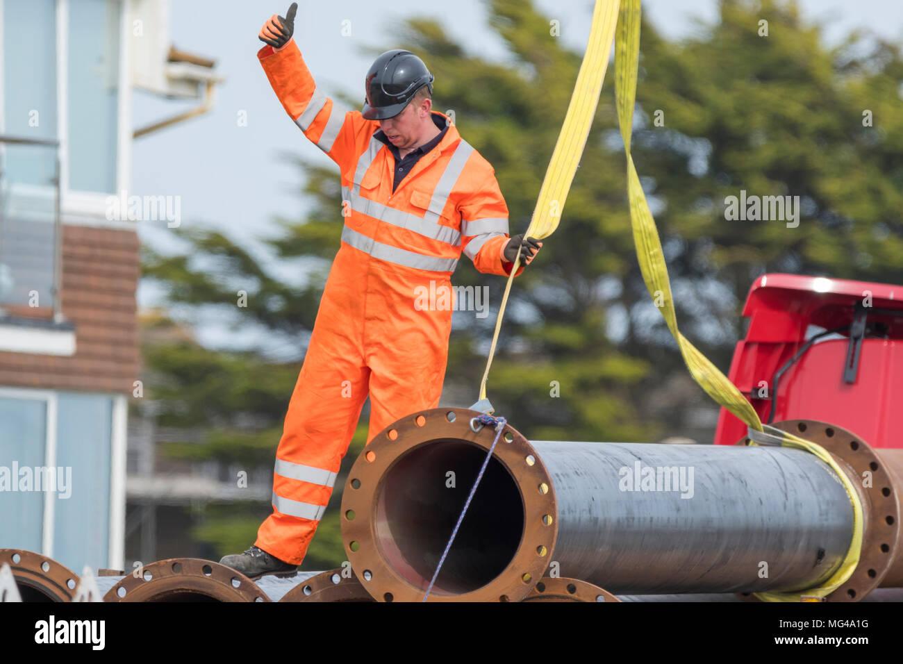 Costruzione maschio lavoratore di indossare abbigliamento protettivo e casco mentre la segnalazione con il pollice fino a un collega per il sollevamento di una tubazione. Immagini Stock