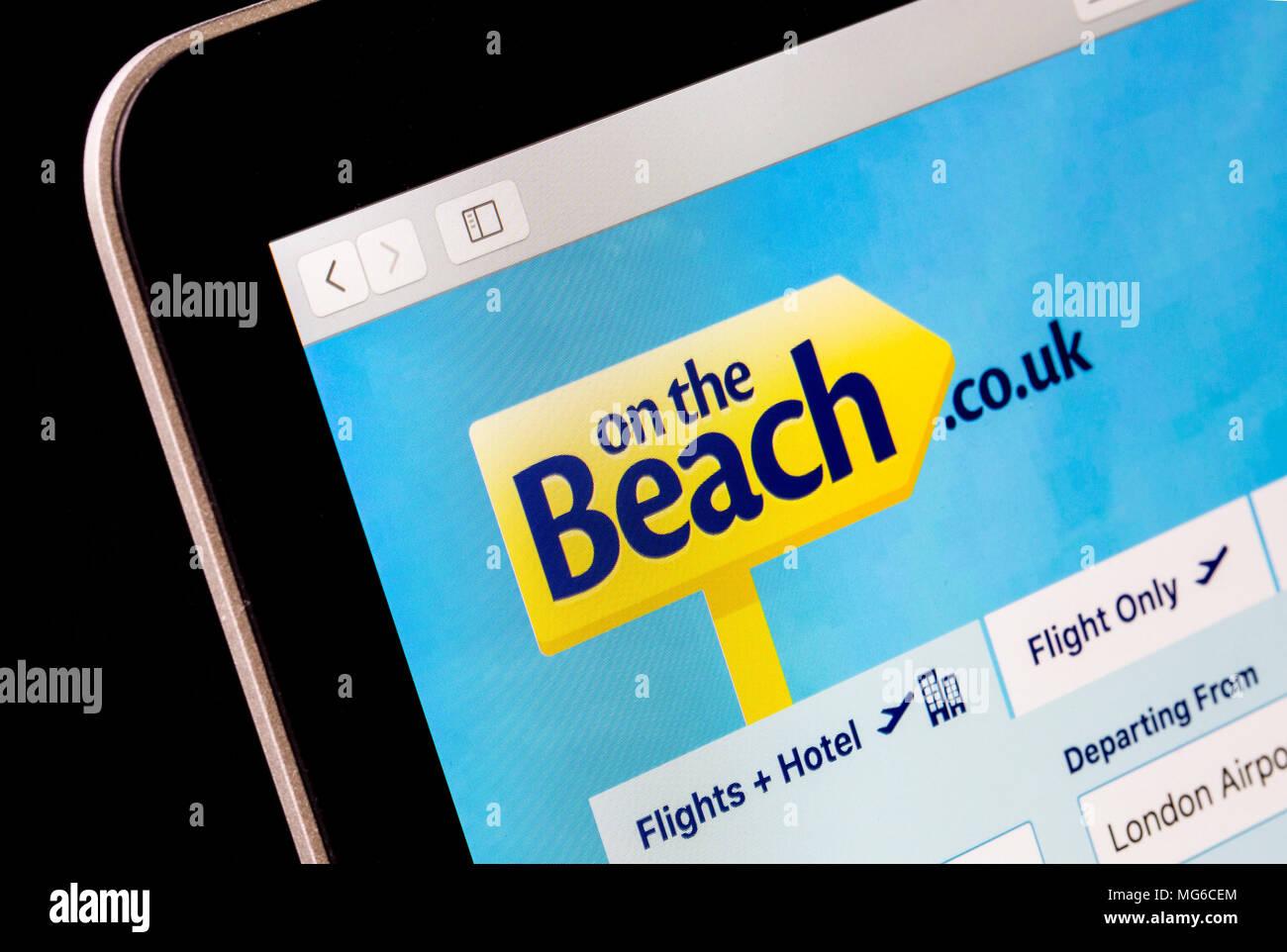 Sulla spiaggia sito web di viaggio su un computer portatile Immagini Stock