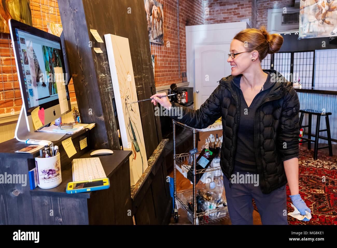 Ammenda artista Katie Maher fa riferimento a un'immagine del computer durante la creazione di un dipinto ad olio nella sua gallery; Salida; Colorado; USA Foto Stock