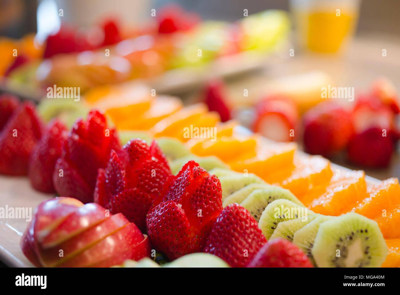 Ordinatamente stabilito prelibatezze di basso contenuto calorico dolci freschi di fettine di mele fragola kiwi e arance sono pronti per qualsiasi tabella di festa durante th Immagini Stock