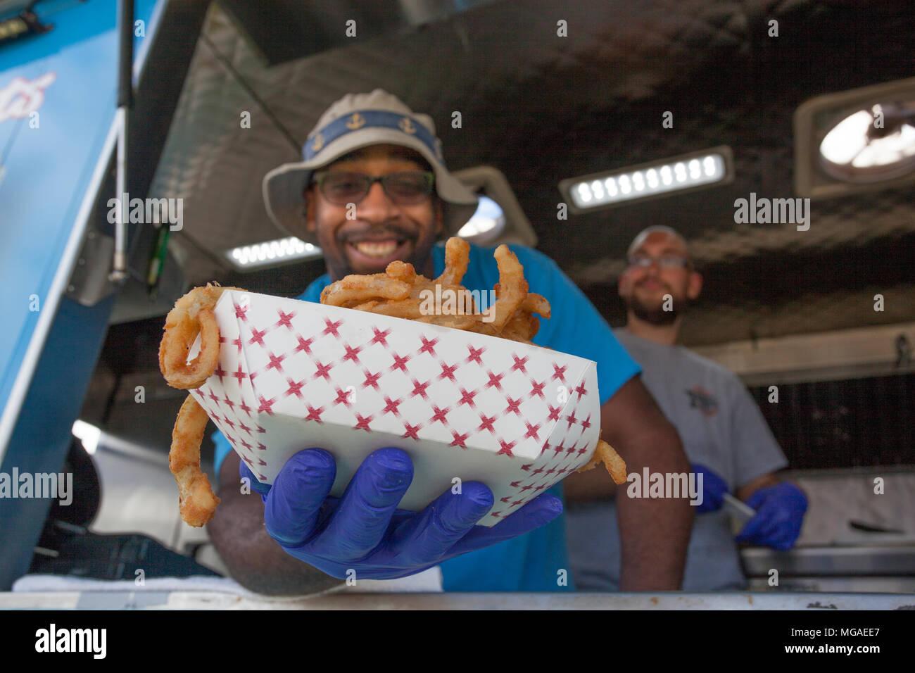 Afro-americano di proprietario di piccola impresa nel suo cibo carrello con un cesto pieno di anelli di cipolla fritti Immagini Stock