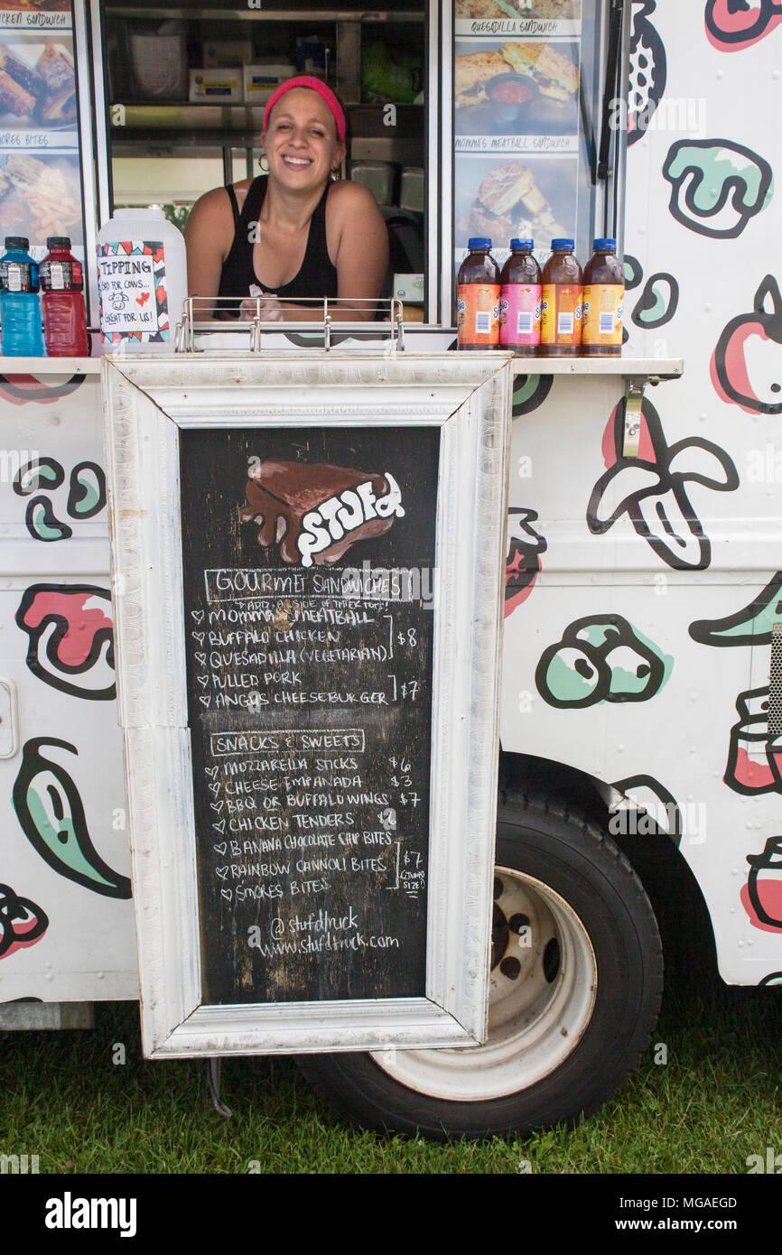 Ritratto di una donna ispanica titolare di una piccola azienda in posa nella finestra del suo cibo sandwich carrello Immagini Stock