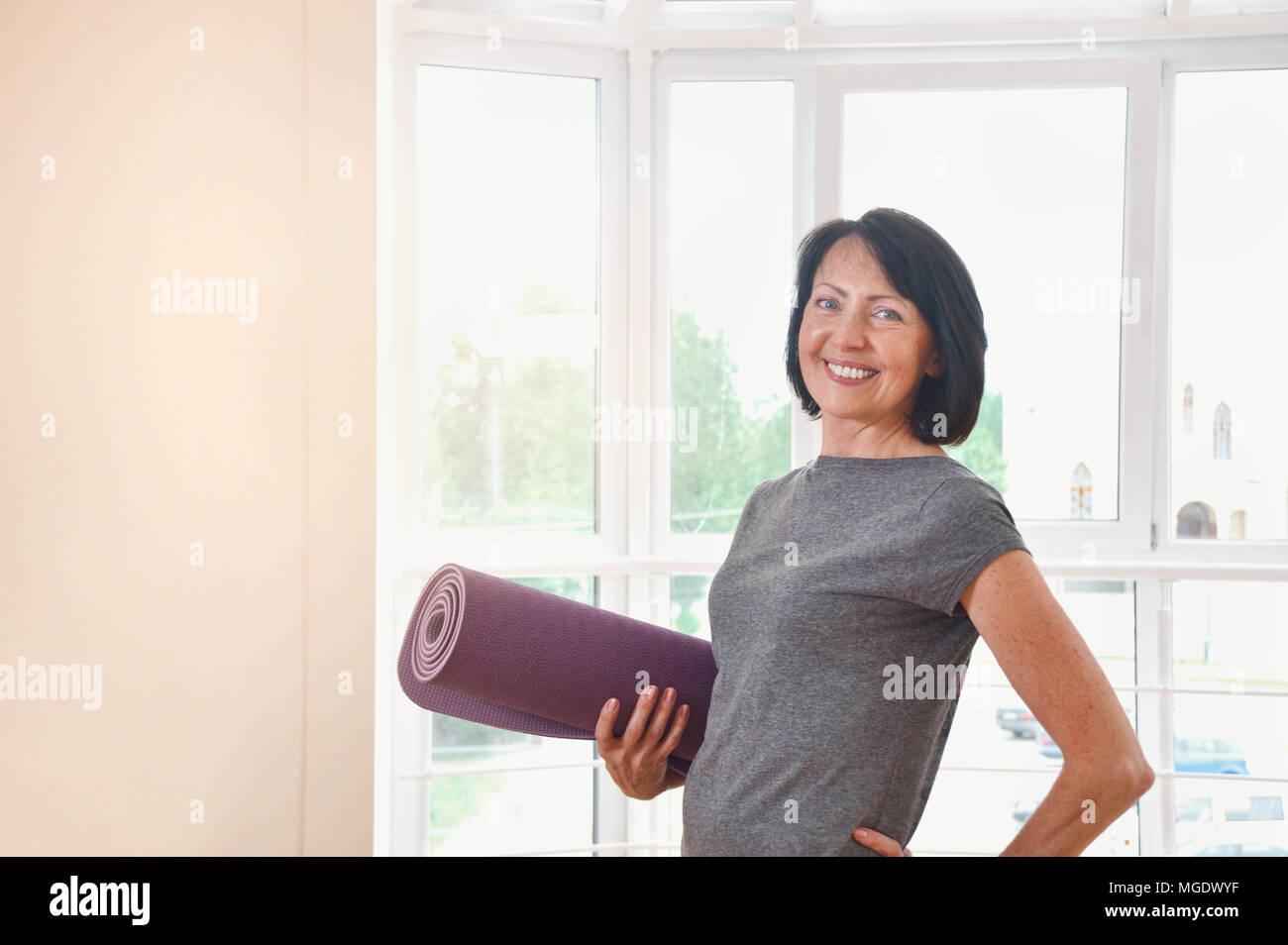 Donna matura azienda arrotolato a esercitare il tappetino in palestra. Allegro femmina istruttore di fitness azienda mat Foto Stock