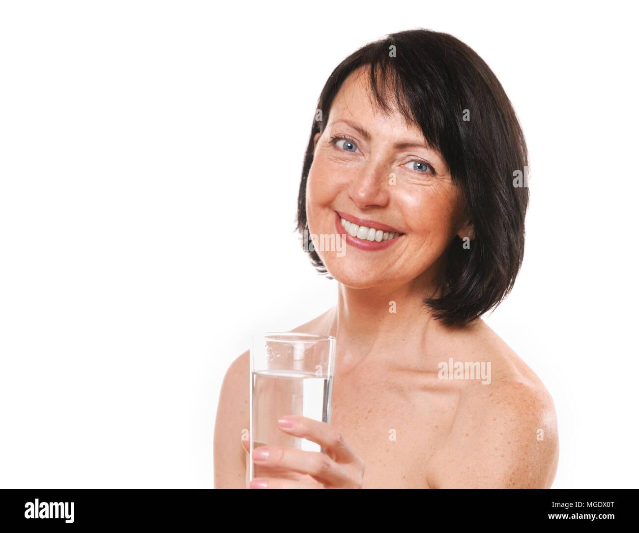Donna matura offrono un bicchiere di acqua. La bellezza e il concetto di cura Foto Stock