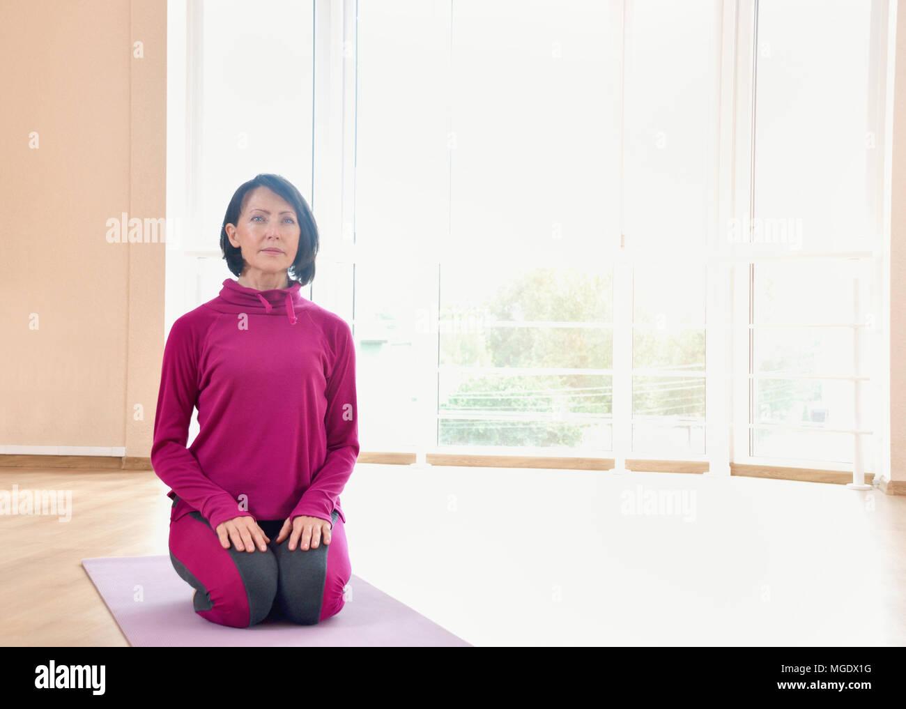 Donna matura sedersi sul tappeto sulle ginocchia. Un sano concetto di fitness con uno stile di vita attivo. Foto Stock