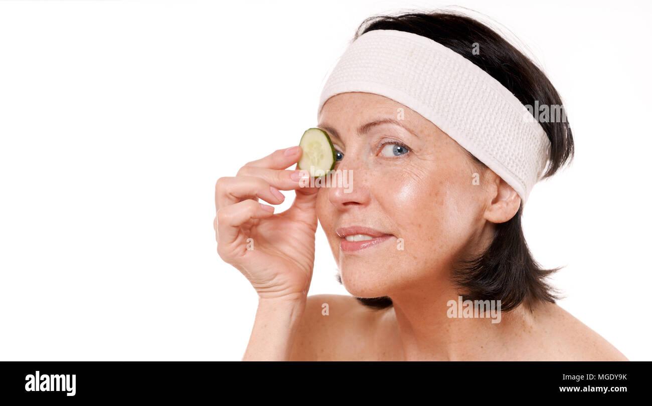 Allegra donna matura azienda pezzo di cetriolo di fronte ai suoi occhi. Natural spa trattamento. Isolato su sfondo bianco Foto Stock