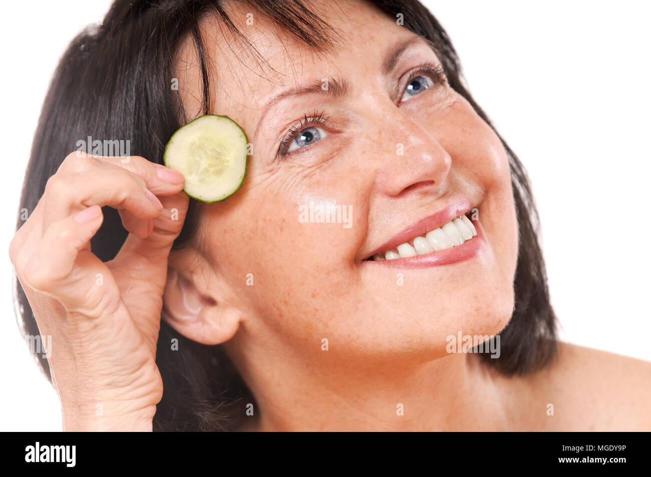 Allegra donna matura tenendo i pezzi di cetriolo vicino agli occhi. Natural spa trattamento. Isolato su sfondo bianco Foto Stock