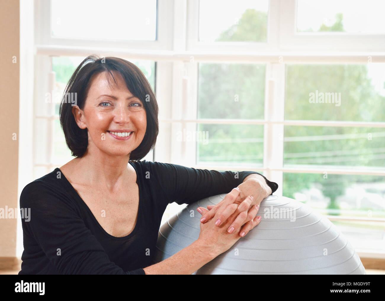 Felice senior donna riposo dopo esercizio. Montare invecchiato povera donna sul grande grigio palla ginnica. Close up ritratto Foto Stock
