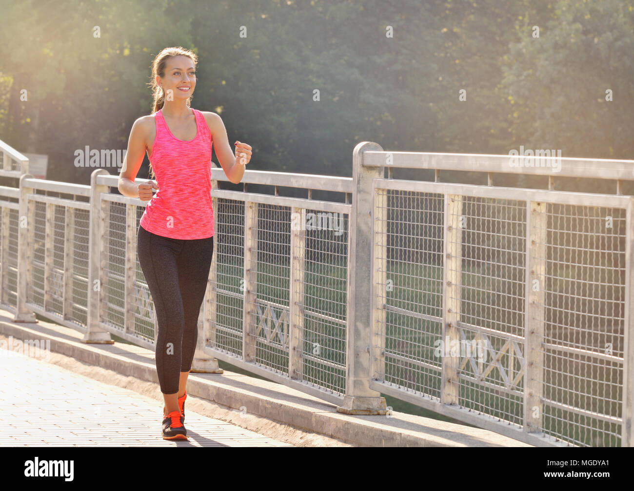 La donna in esecuzione sul ponte. Runner donna jogging sulla strada urbana della formazione per la maratona. Montare ragazza fitness modello atleta esercizio outdoor Foto Stock