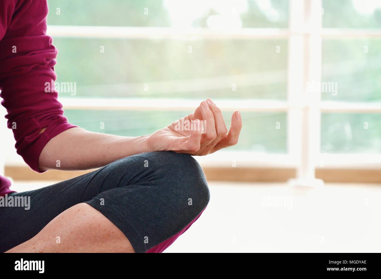 Donna matura seduta sul pavimento nella posizione del loto. Un sano concetto di fitness con uno stile di vita attivo. Close up Foto Stock