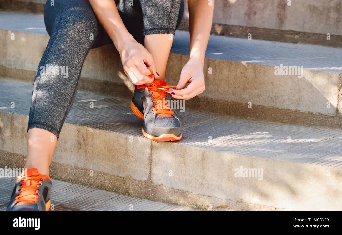 La donna la legatura dei lacci delle scarpe da corsa prima del training seduti sulle scale. Uno stile di vita all'aperto di close-up delle gambe del giovane sportivo da donna Foto Stock