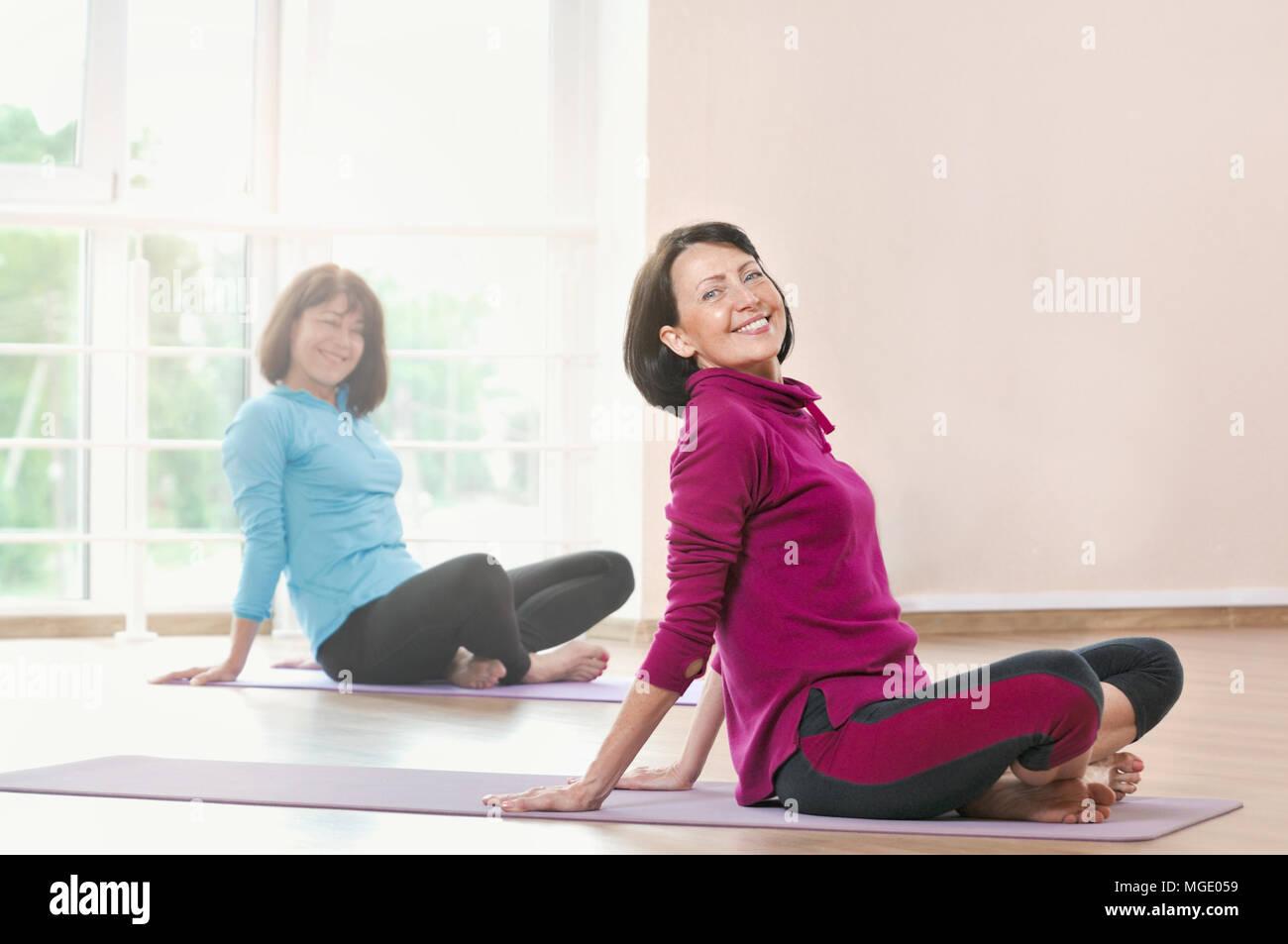 Attiva le donne sportive fare esercizio in palestra. Due donne facendo esercizi di stretching e la pratica dello yoga in studio con grandi finestre su sfondo Foto Stock