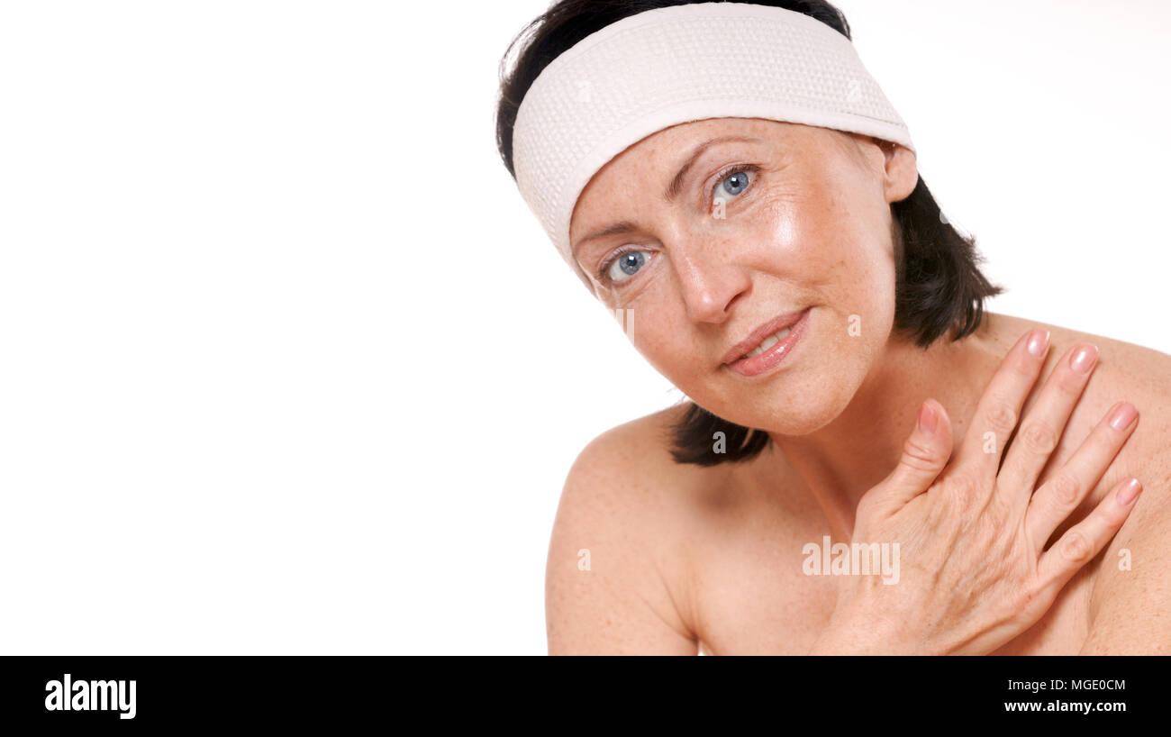 Spa ritratto di attraente sorridente donna matura. Isolato su bianco. Studio shot Foto Stock