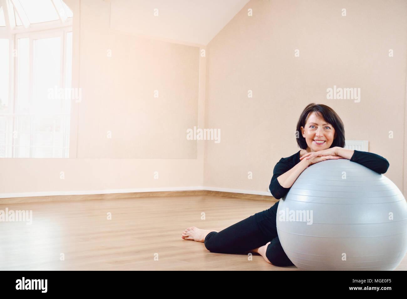 Felice senior donna riposo dopo esercizio. Montare invecchiato povera donna sul grande grigio palla ginnica. Foto Stock