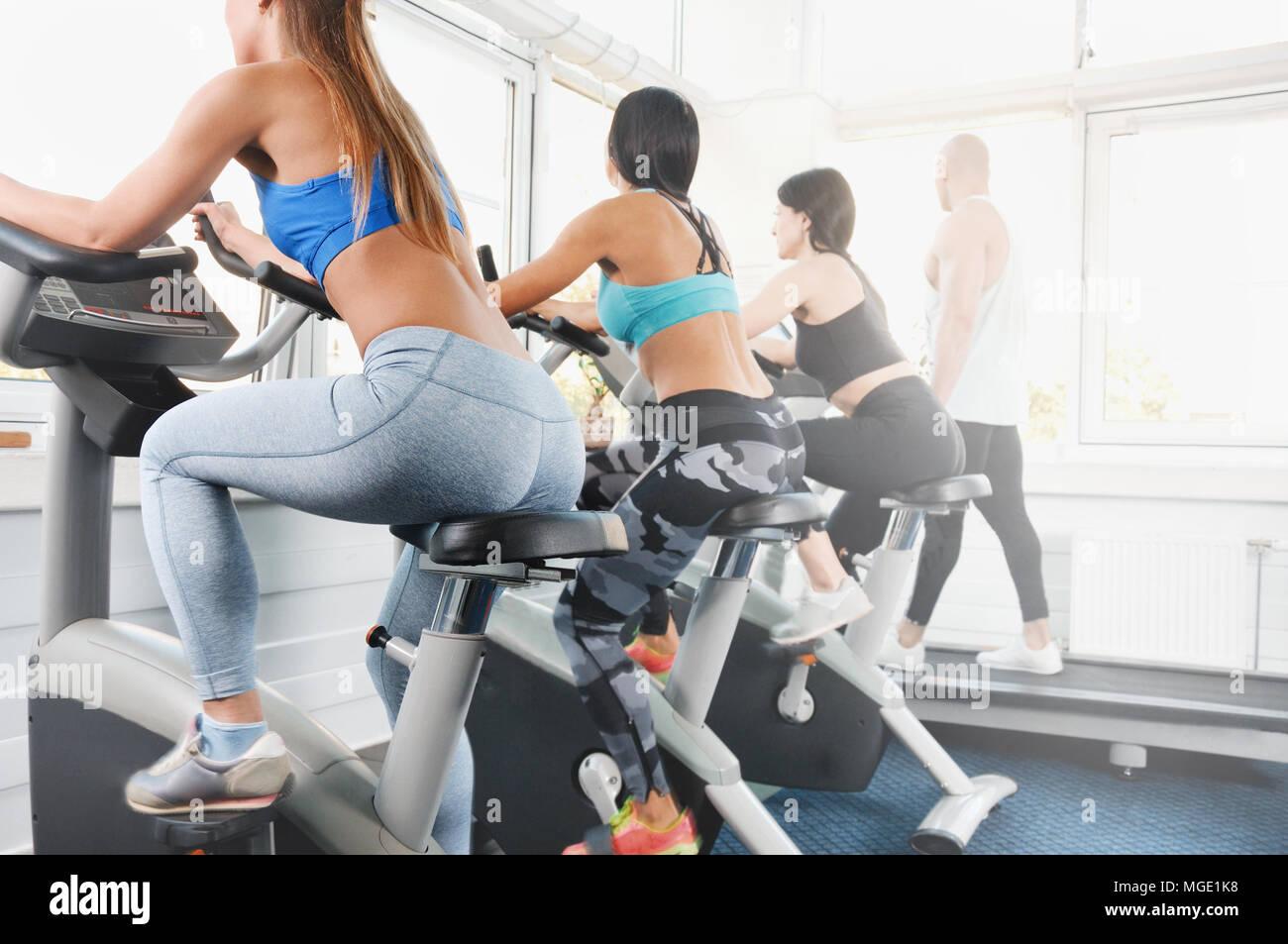 Un gruppo di quattro persone in palestra, esercitando le loro gambe facendo cardio-training. Idoneità delle giovani donne e un uomo su palestra bike Foto Stock