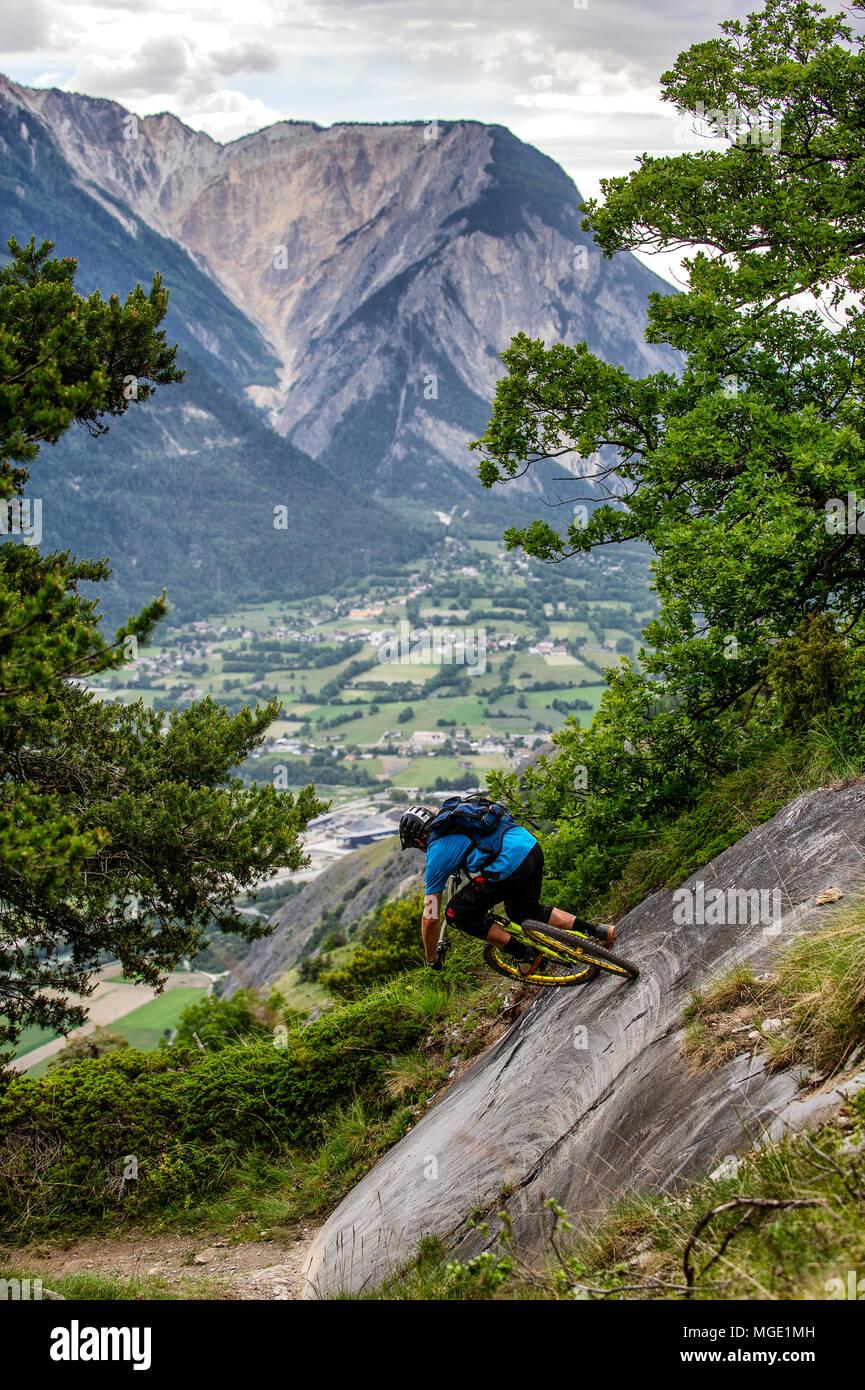 Un uomo corse in mountain bike in alto sopra il piano della valle in prossimità della città di Gampel e Jeizinen in Vallese della Svizzera. Foto Stock
