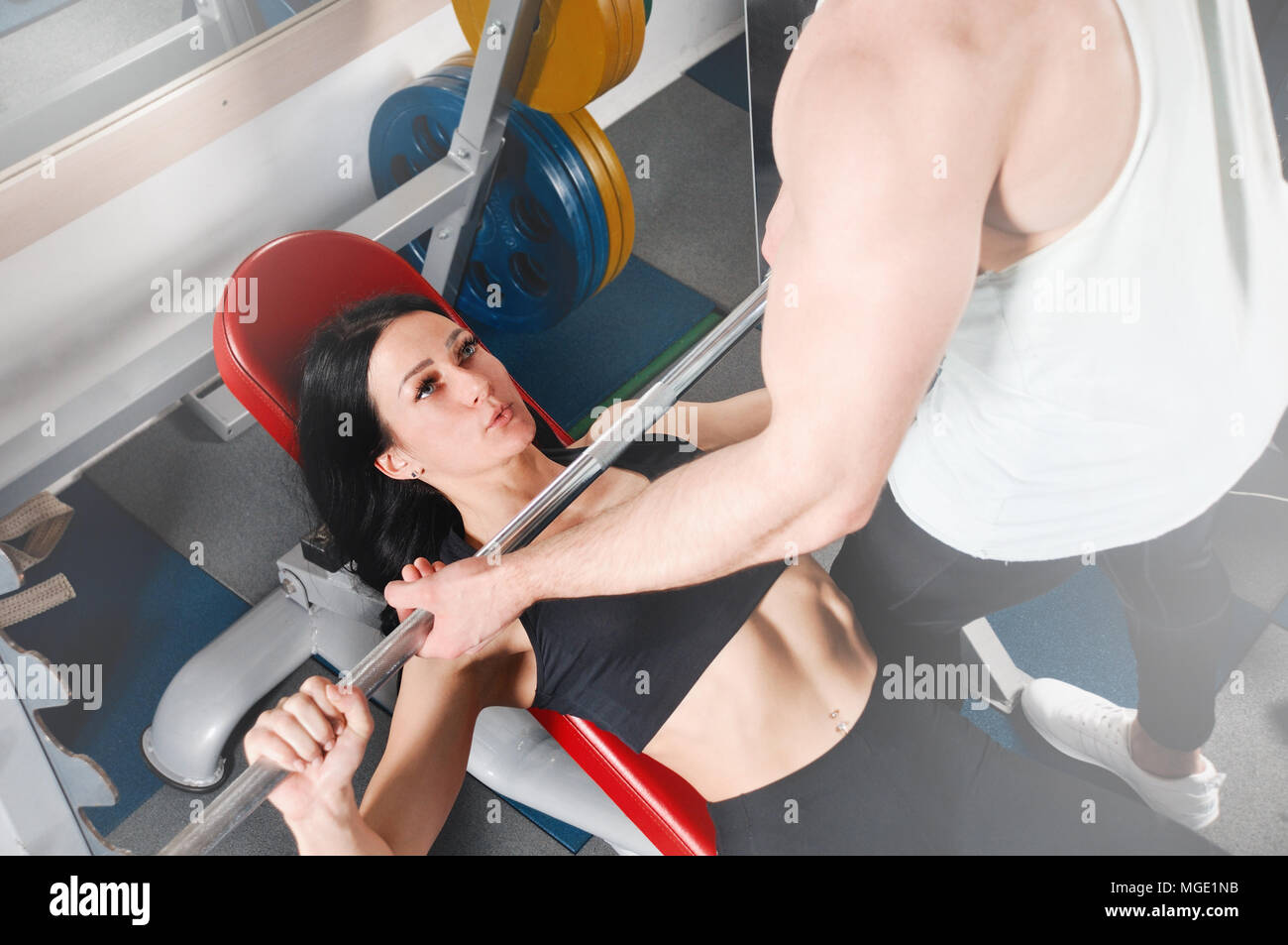 Giovane donna e personal trainer con barbell flettendo i muscoli in palestra. Attraente giovane donna sportivo sta lavorando in palestra Foto Stock