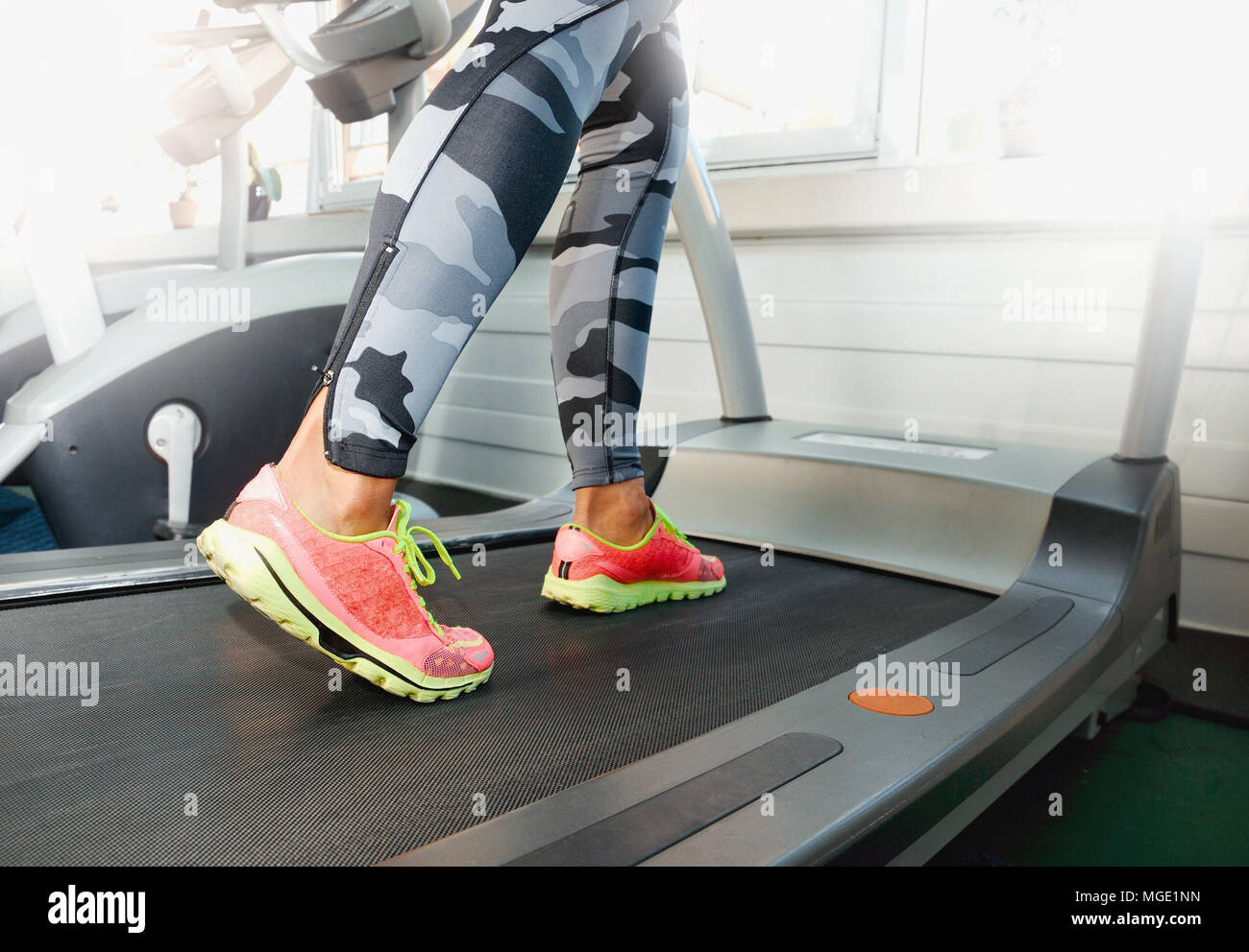 Close up della donna in piedi in scarpe colorate in esecuzione sulla macchina tapis roulant in palestra. Centro fitness training. Uno stile di vita sano concetto. Foto Stock