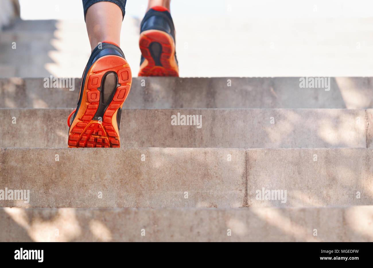 Basso angolo posteriore del ritratto femminile in azione su scala Foto Stock