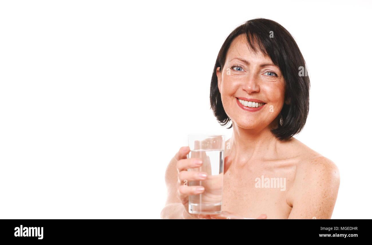 Donna matura tenere il vetro di acqua. La bellezza e il concetto di cura Foto Stock