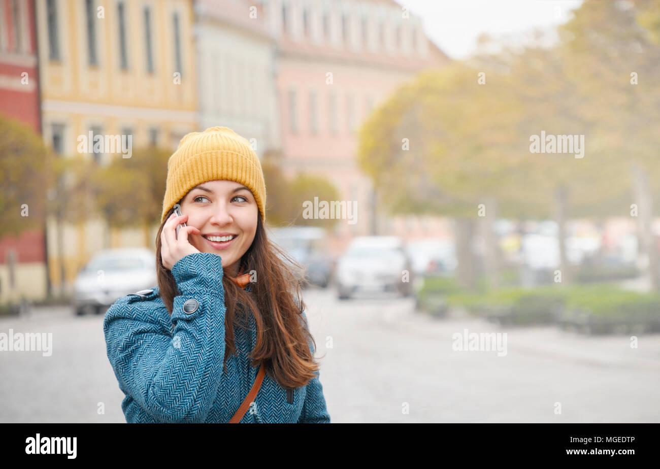 Giovane e bella donna che parla al telefono su Wroclaw street. La ragazza di blue coat e caldo hat posti esterni di chiamata sul telefono Foto Stock