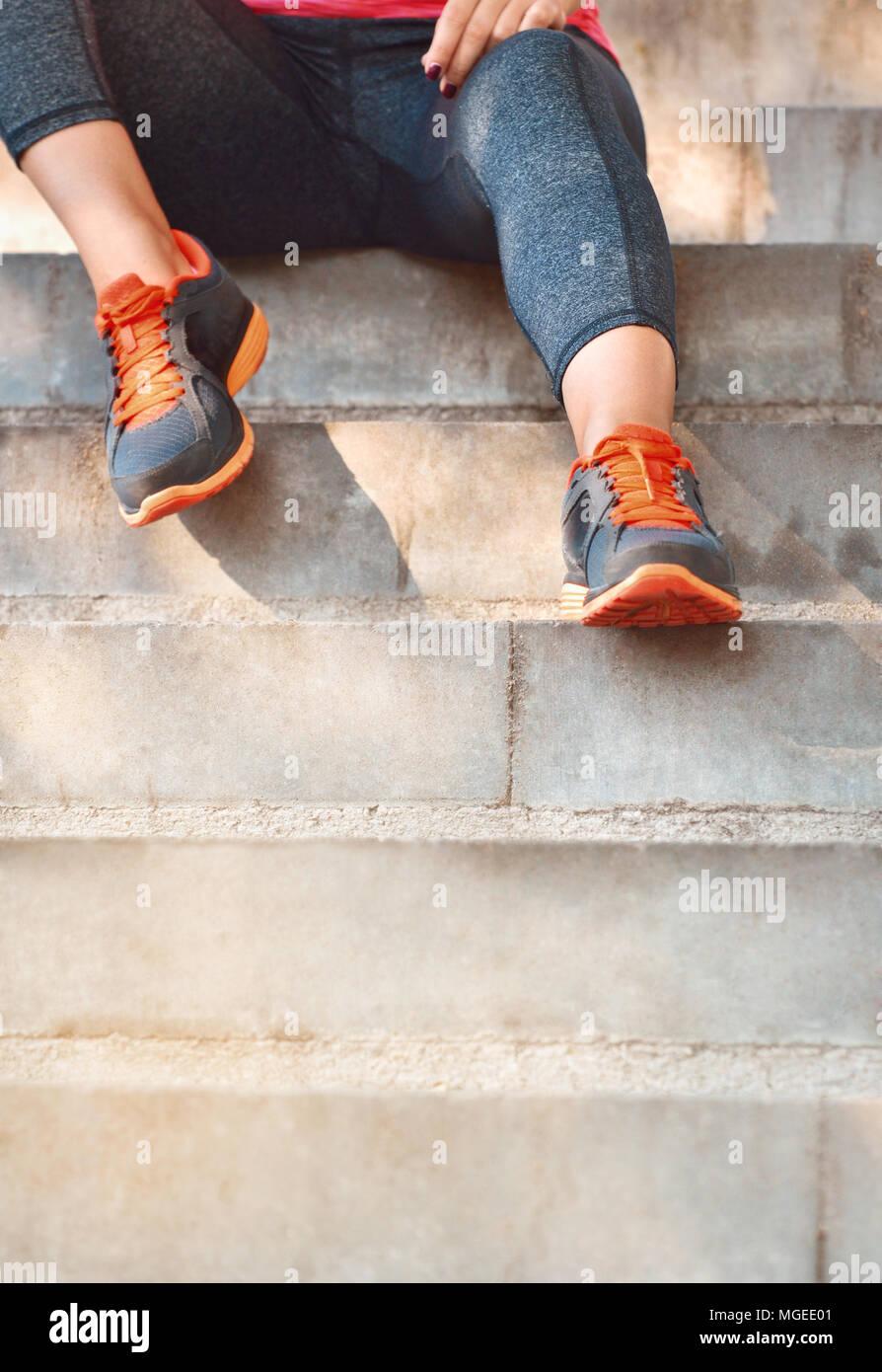 Close up dei womans calzature sportive. Giovane donna seduta sulle scale. Uno stile di vita sano Foto Stock