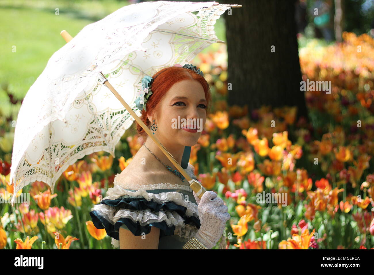 Una donna con i capelli rossi e un ombrellone bianco per proteggersi dal sole si rilassa in un campo di rosso e tulipani gialli Foto Stock