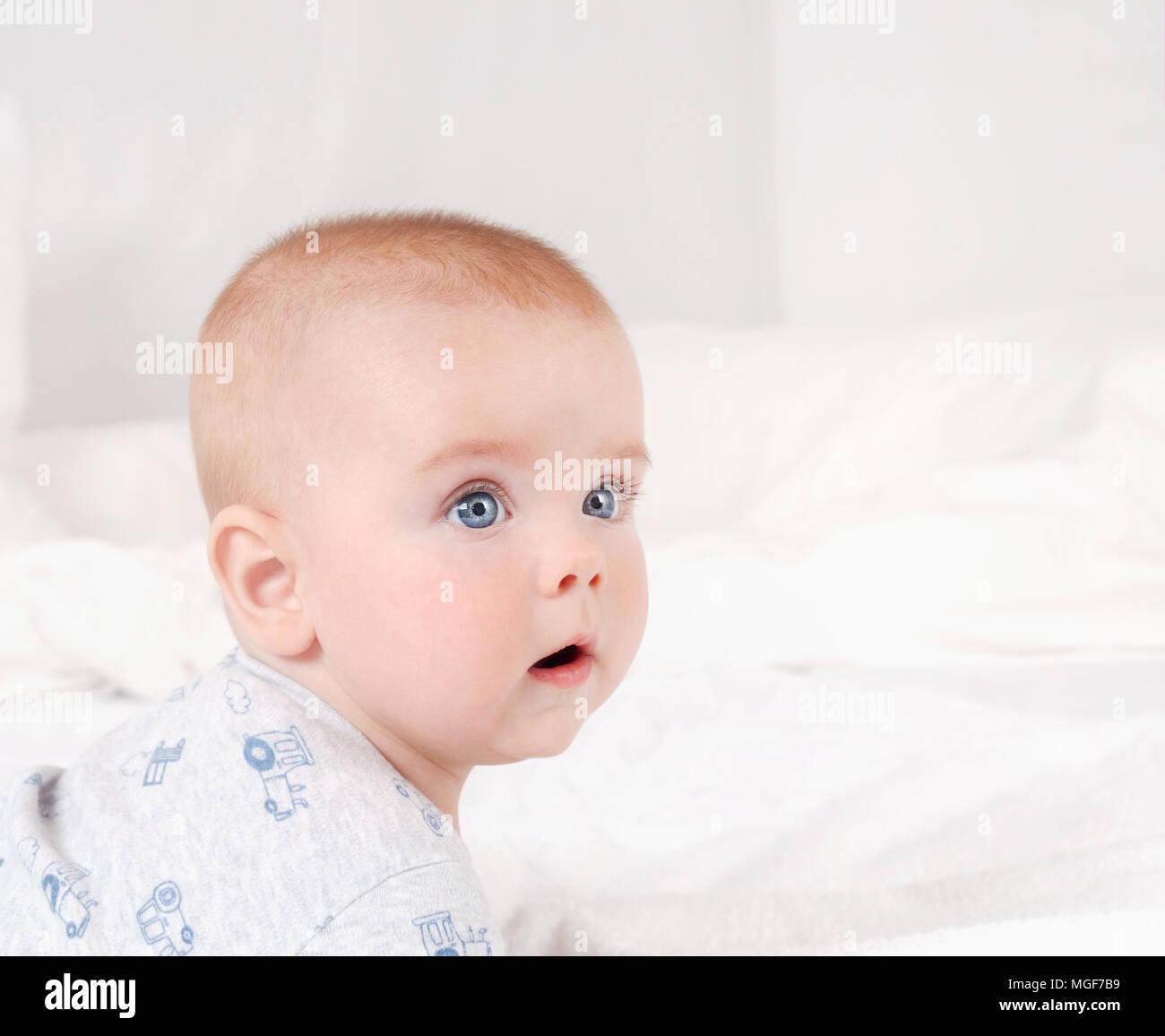 Closeup ritratto di neonato adorabile. Sorridenti bambino con gli occhi blu su bianco sullo sfondo del letto Foto Stock