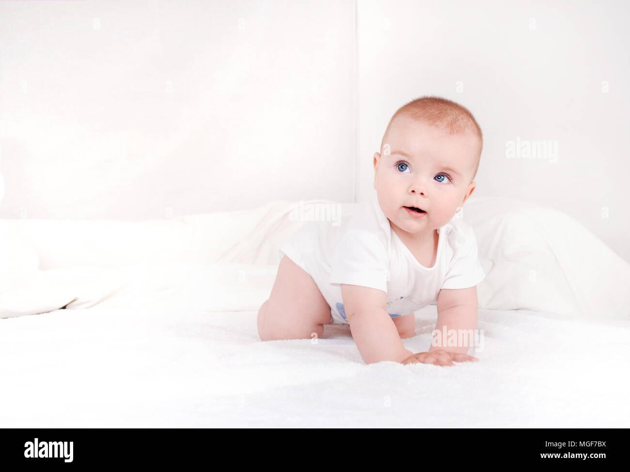 Ritratto di dolce neonato crawlng sul letto bianco grave alla ricerca di distanza. Sorridenti bambino con gli occhi blu su bianco sullo sfondo del letto Foto Stock