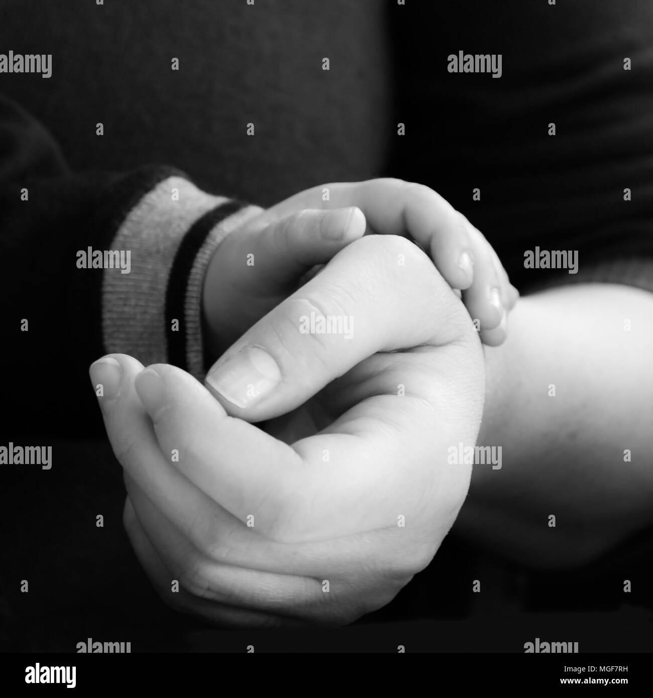 Bambino tenendo la sua madre la mano. Concetto di purezza e di amore. Immagini Stock