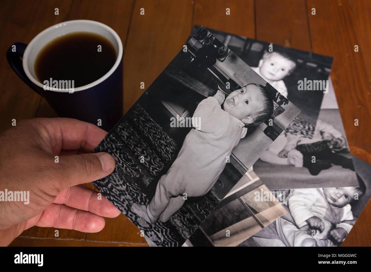 Una persona cerca attraverso vecchie foto con una sensazione di nostalgia. Immagini Stock