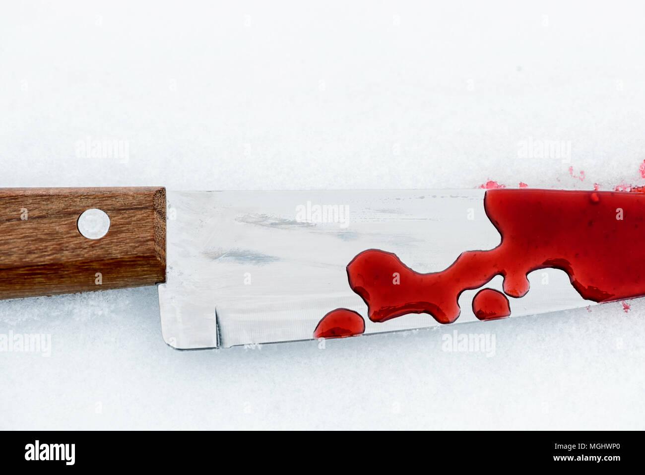 Metallo affilato coltello da cucina bordo utilizzato come un violento omicidio arma con gocce di sangue su un bianco della neve sullo sfondo. Lama rivestita in violenza con spazio di copia Immagini Stock