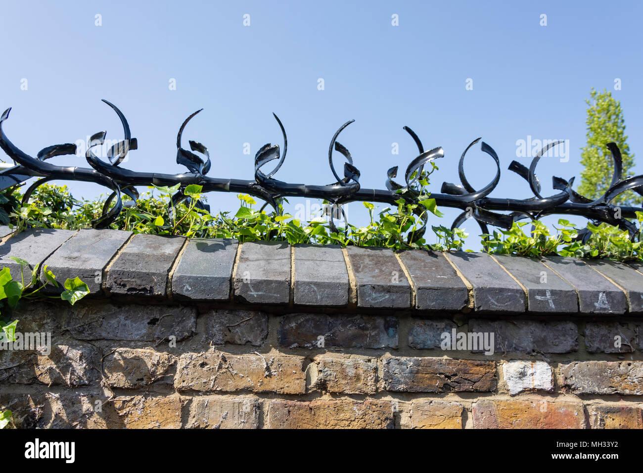 Protezione in metallo spike sul muro del giardino, Chiswick, London Borough di Hounslow, Greater London, England, Regno Unito Immagini Stock