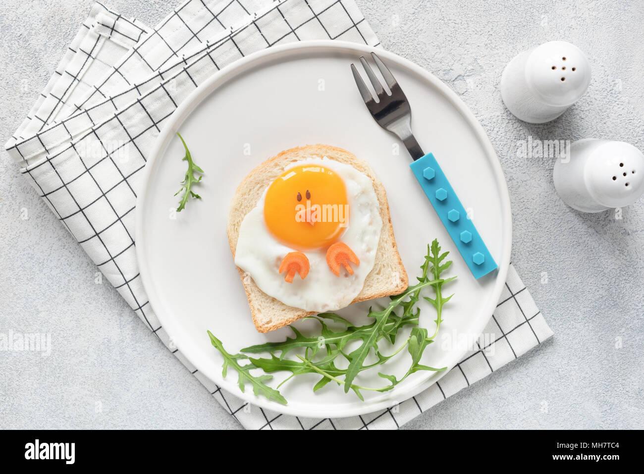Carino divertente la prima colazione per i bambini. A forma di pollo sandwich o toast sulla piastra bianca. Arte cibo idea. Lay piatto. Tabella vista superiore Immagini Stock
